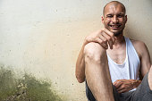 Smiling homeless, Young skinny anorexic bald positive and happy smiling homeless man sitting on the urban street in the city or town near white wall with big smile, homelessness social documentary con