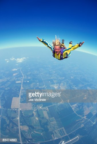 Young skydiver in freefall above patchwork fields. : Stock Photo