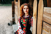 Young Slavonic woman in traditional embroidered costume and red shoes sitting on the porch