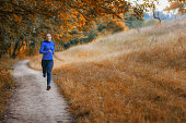 young slim athleic jogger in a black sports leggins and and blue jacket  runs along the path  on the  beautiful  autumnal forest. Photo show  active healthy lifestyle.