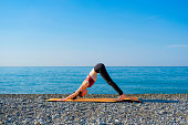 Young slim woman in tight sportswear standing in Downward-Facing Dog pose on orange yoga mat outdoors at pebble beach by the sea. Yoga at nature concept.