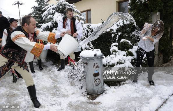 Young Slovak men dressed in traditional costumes pour a bucket with cold water over a woman as part of Easter celebrations in the village of...