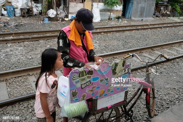 A young slum dweller girl buys ice cream from a vendor on a bicycle on the rairoad track in Kota City on November 25 2016 in Jakarta Indonesia The...