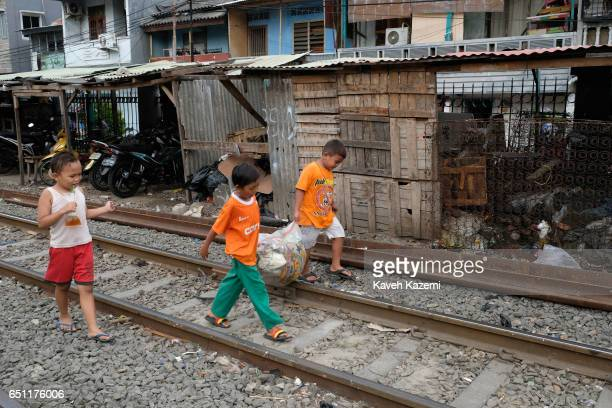 Young slum dweller kids carry recycle waste in a plastic bag while walking on the rairoad track in Kota City on November 25 2016 in Jakarta Indonesia...