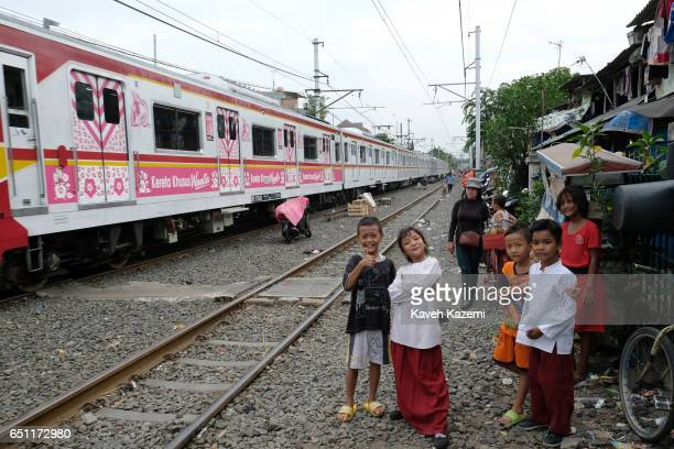 Young slum dweller kids pose for the camera while a trains speeds away on the rairoad track in Kota City on November 25 2016 in Jakarta Indonesia The...