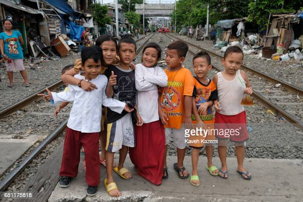 Young slum dweller kids pose for the camera while standing between the rairoad tracks in Kota City on November 25 2016 in Jakarta Indonesia The slum...