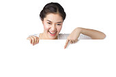 Young smiley Asian woman showing and pointing at blank billboard sign banner isolated on white background.