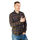 Young smiling bearded man in a checkered shirt showing direction with finger. Isolated on white background