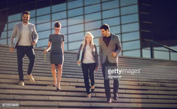 Young smiling business people walking down the stairs.