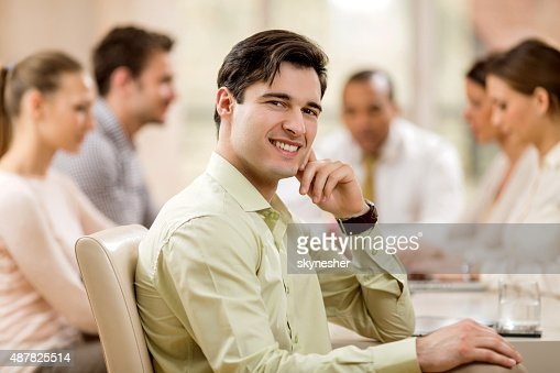 Young smiling businessman on a meeting looking at camera.