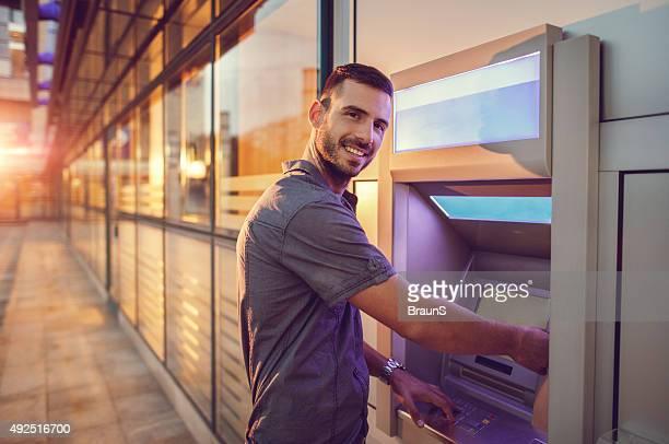 Homme d'affaires jeune souriant retirer de l'argent à un distributeur automatique de billets.