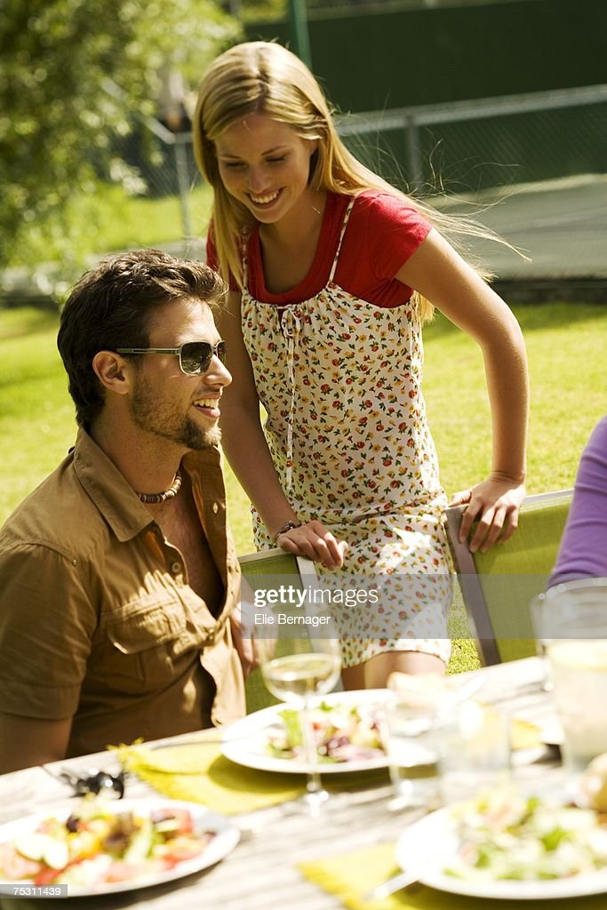 Young smiling couple at garden table : Stock Photo