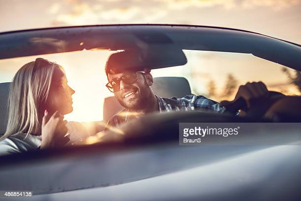 Young smiling couple enjoying while driving in cabriolet at suns
