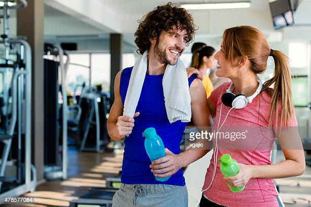 Young Smiling Couple in a gym with towel around neck.