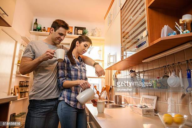 Young smiling couple in the kitchen.