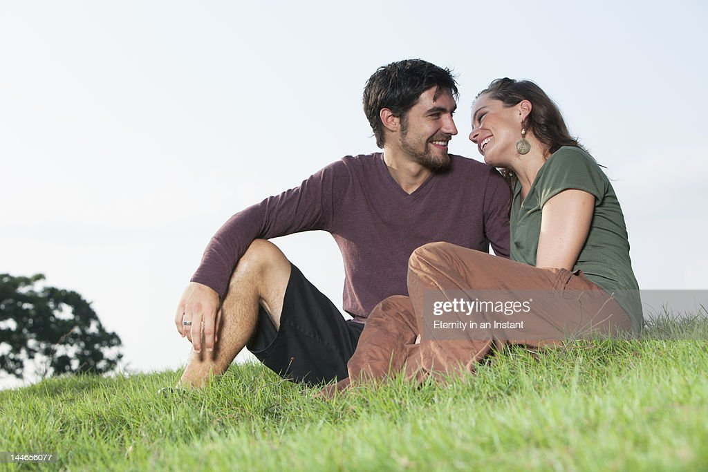 Young smiling couple outdoors sitting on the grass : Stock Photo