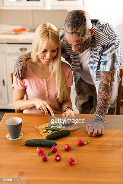 Young smiling couple preparing healthy food in the kitchen.