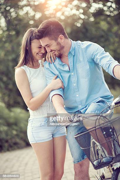 Young Smiling Couple Pushing Bicycle Together in the Park