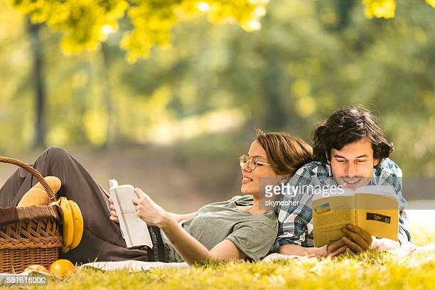 Young smiling couple reading books on picnic in nature.
