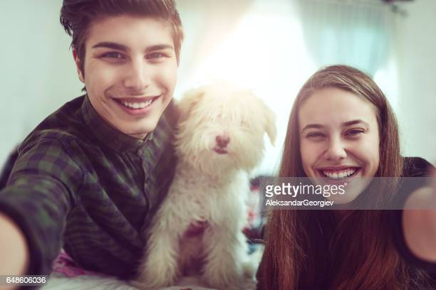 Young Smiling Couple Taking Selfie with Their Dog