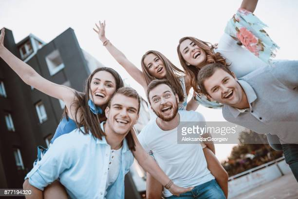 Young Smiling Couples Having Fun in City with Piggyback Ride