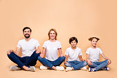 Young smiling family, bearded father, blonde mother, boy and girl wearing blue jeans and white T-shirts, sitting in odrer of hierarchy in lotus pose
