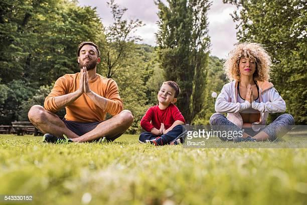 Jeune souriant famille faisant du Yoga exercices de détente sur une herbe.