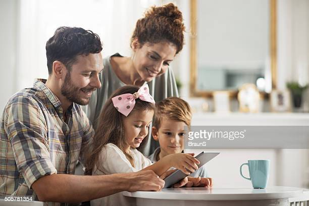 Young smiling family using touchpad at home.