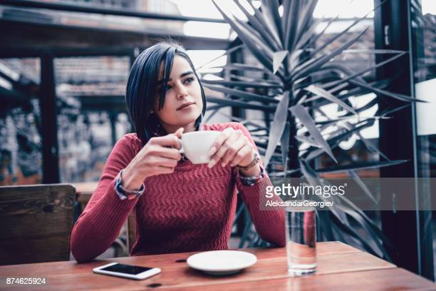 Young Smiling Female Enjoying Coffee Break at the Restaurant