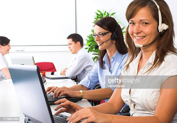 Young smiling female helpdesk operator in foreground
