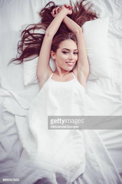 Young Smiling Female couché et Waking up dans sa chambre