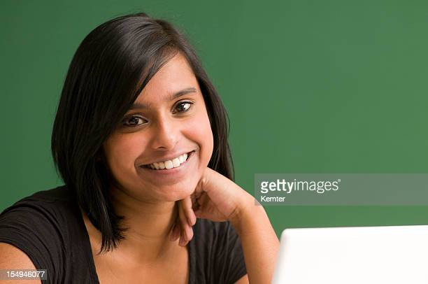 Young, Smiling Female Teacher in Front of Blackboard