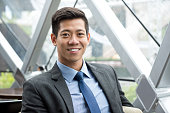 Young smiling handsome Asian Thai-Chinese businessman sitting at office lounge