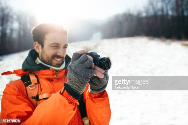 Young smiling hiker photographing winter landscape