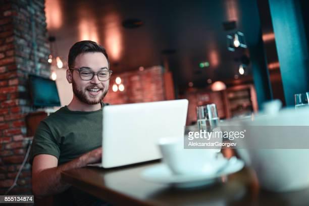 Junge lächelnde Hipster-Freelancer arbeitet in einem Cafe-Restaurant
