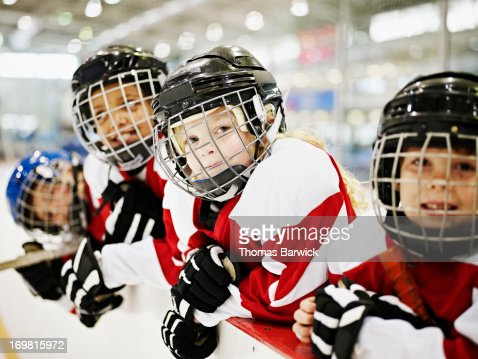 Young smiling ice hockey players in players box