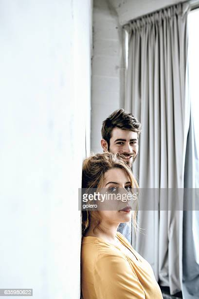 young smiling man and pensive beautiful woman looking into camera
