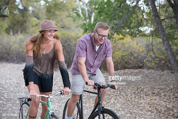 A young, smiling man and woman riding bicycles in a park for fitness