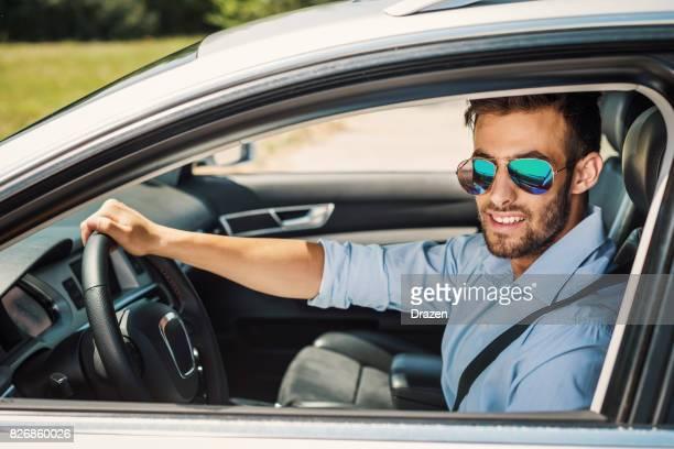 Jeune homme souriant, location de voiture au volant