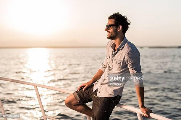 Giovane uomo sorridente godendo di un giorno su uno yacht.