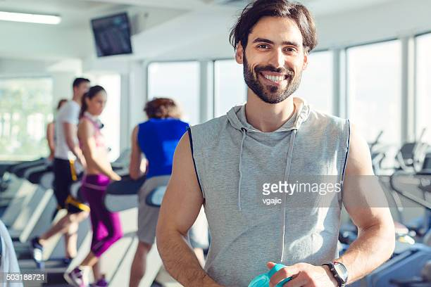 Young Smiling Man in a gym holding bottle.