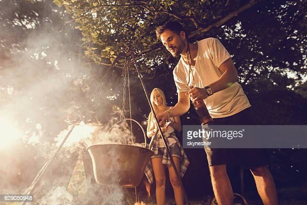 Young smiling man preparing food in the forest.