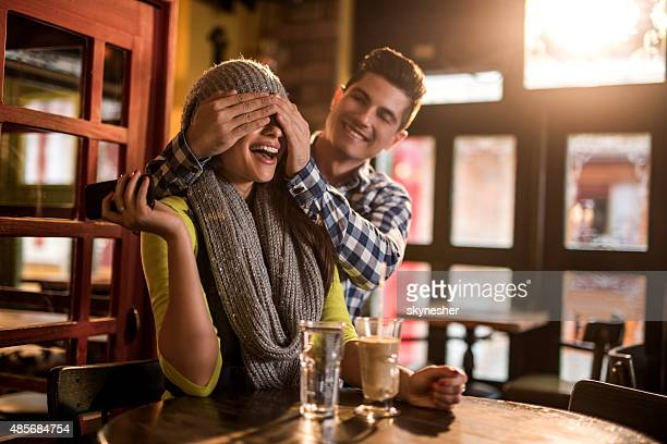 Young smiling man surprising his girlfriend in a cafe.