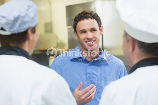 Young smiling manager talking to the staff : Stock Photo
