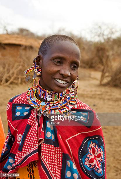 Young smiling Masai woman in front of her village, Kenya.