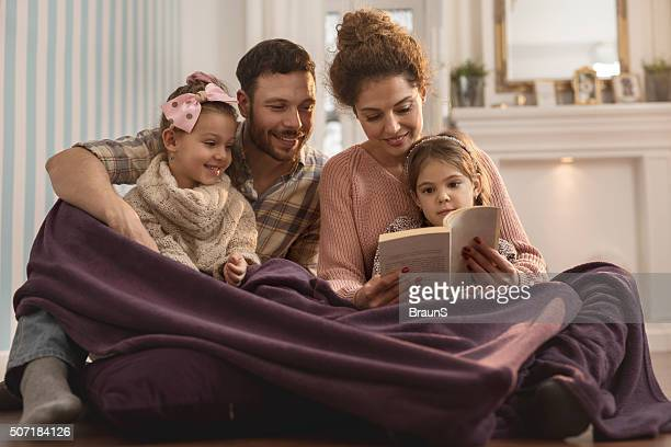 Young smiling parents reading a book to their small daughters.