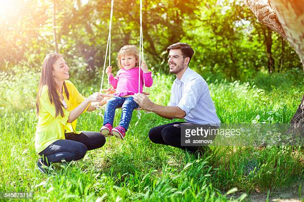 Young smiling parents swinging their daughter in the park
