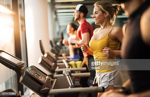 Young smiling people running on treadmills in a health club.