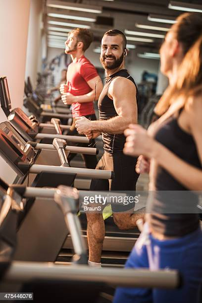 Young smiling people running on treadmills in health club.