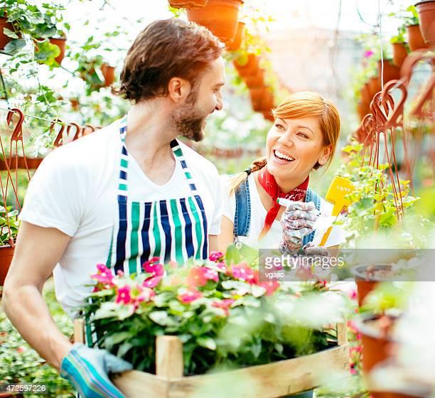 Junge lächelnde Menschen arbeiten in Gartenbau-Betrieb beginnen.
